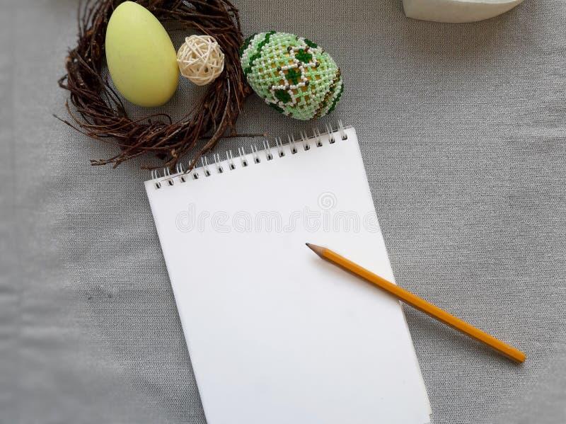 Couleurs en pastel et oeufs de p?ques d?cor?s, guirlande et carnet vide avec le crayon sur le fond gris de tissu photo stock