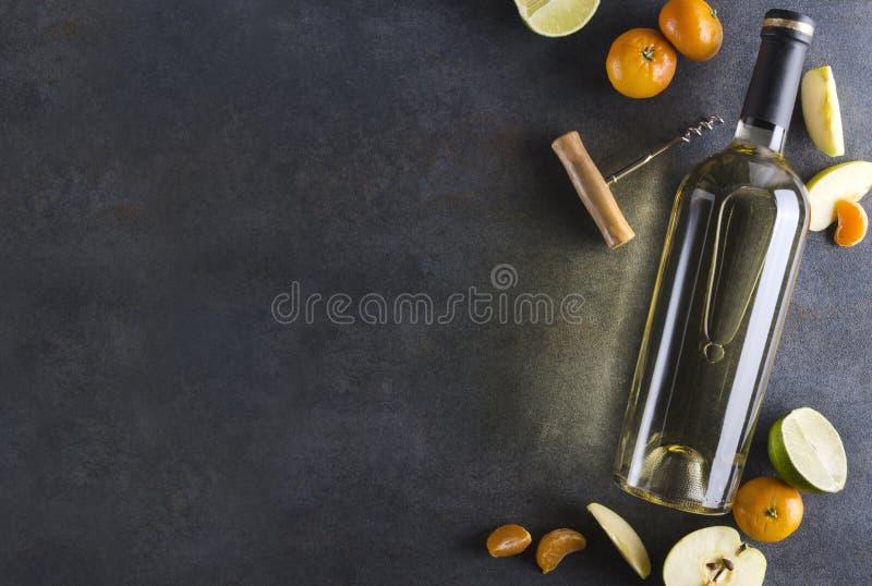Couleurs fonc?es, lumi?res brillantes Bouteille de vin blanc entour?e par les fruits d?licieux et juteux sur la surface rustique  image stock