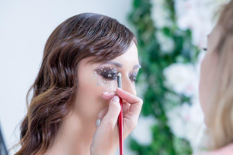 Coulissescène: Professionele Grimeur die glamour modelmake-up doen op het werk Maakt de schoonheids modelvrouw met mooi stock afbeeldingen