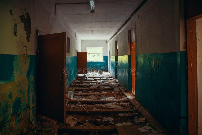 Couloir rampant sombre avec des portes et plancher cassé dans le vieux bâtiment abandonné effrayant, vue de tunnel photographie stock