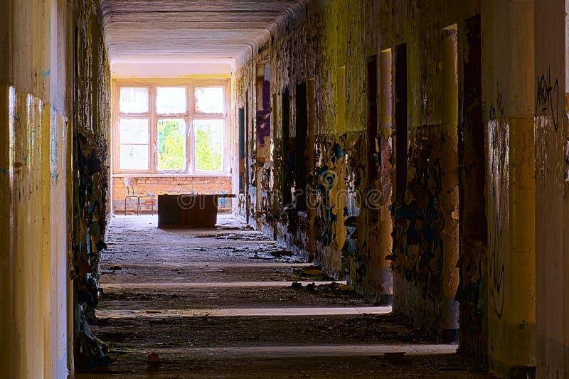 Couloir sale dans un bâtiment abandonné avec la lumière venant des salles vers la droite photos libres de droits