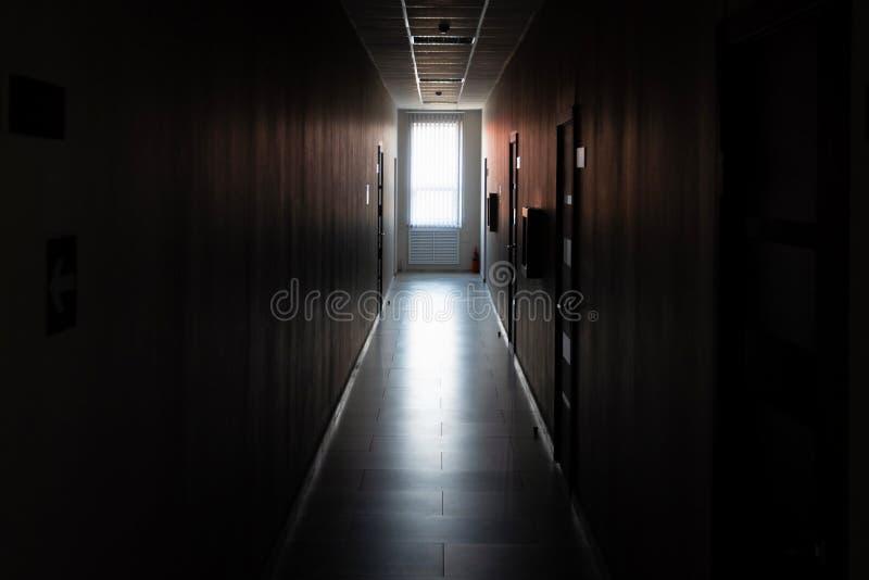 Couloir sombre avec des portes et lumière de fenêtre à la fin photo stock