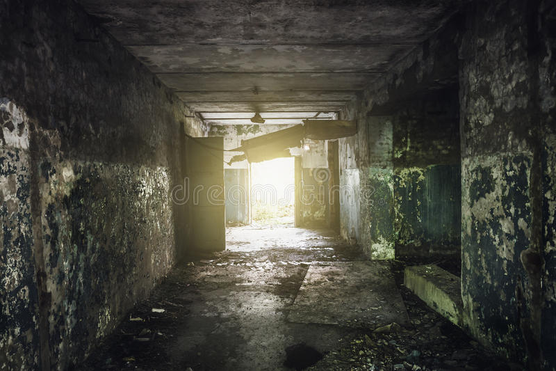 Couloir sombre avec la peinture d'épluchage sur les murs dans un bâtiment abandonné photo stock