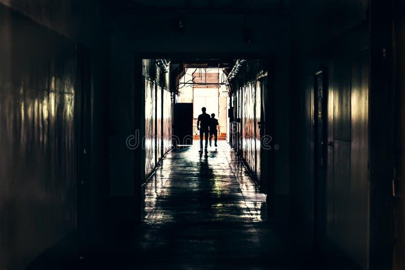 Couloir sombre dans le bâtiment, les portes et les silhouettes de pour deux hommes, perspective photo libre de droits