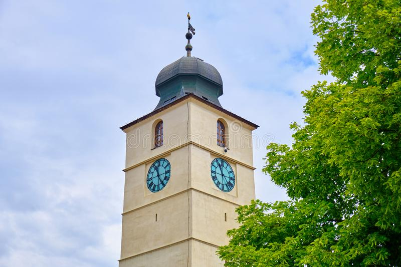 The Council Tower Turnul Sfatului in Sibiu Small Square Piata Mica - top part with a green tree, on a bright day. Popular touristic landmark in Hermannstadt royalty free stock images