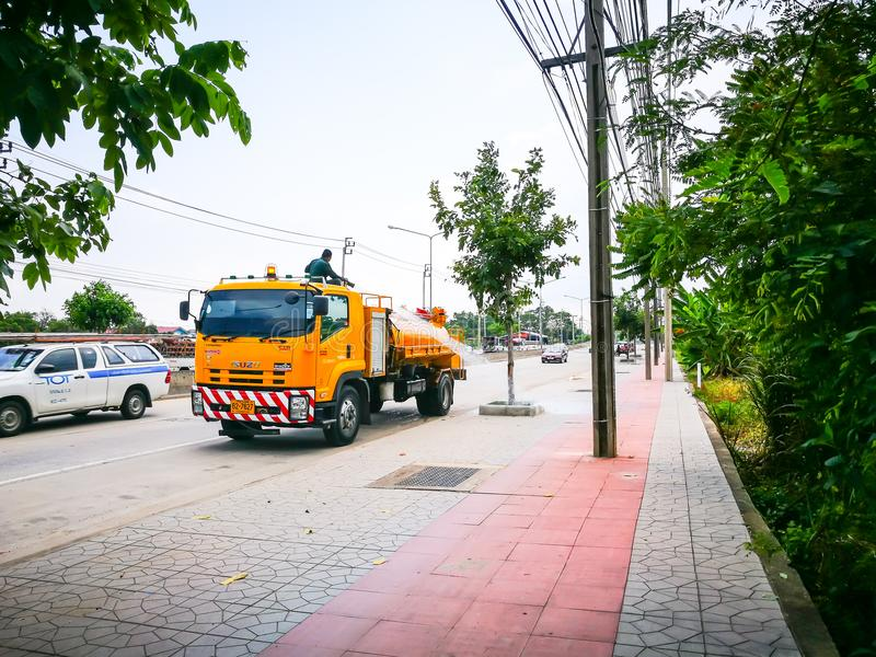 Council worker using water truck Pump for pouring water to the tree at footpath. stock image