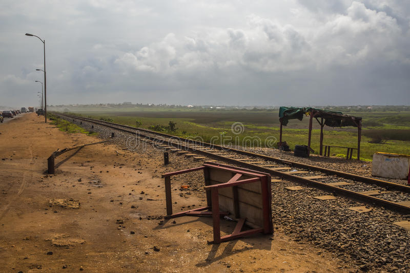 Counrty life in Ghana (West Africa). Old rail line and near the Beach Road between Tema and Accra in Ghana (West Africa). There is a fallen workbench on the royalty free stock photography