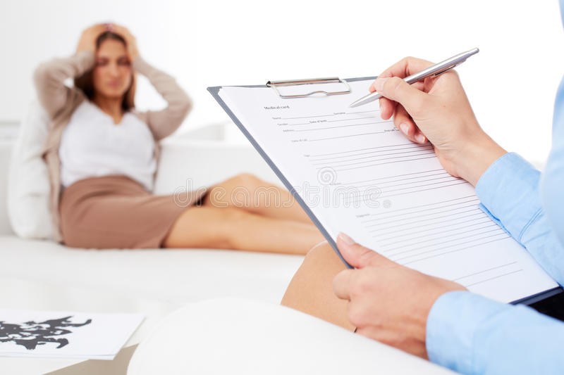 Counseling. Professional psychiatrist consulting her patient and making notes in application form stock images