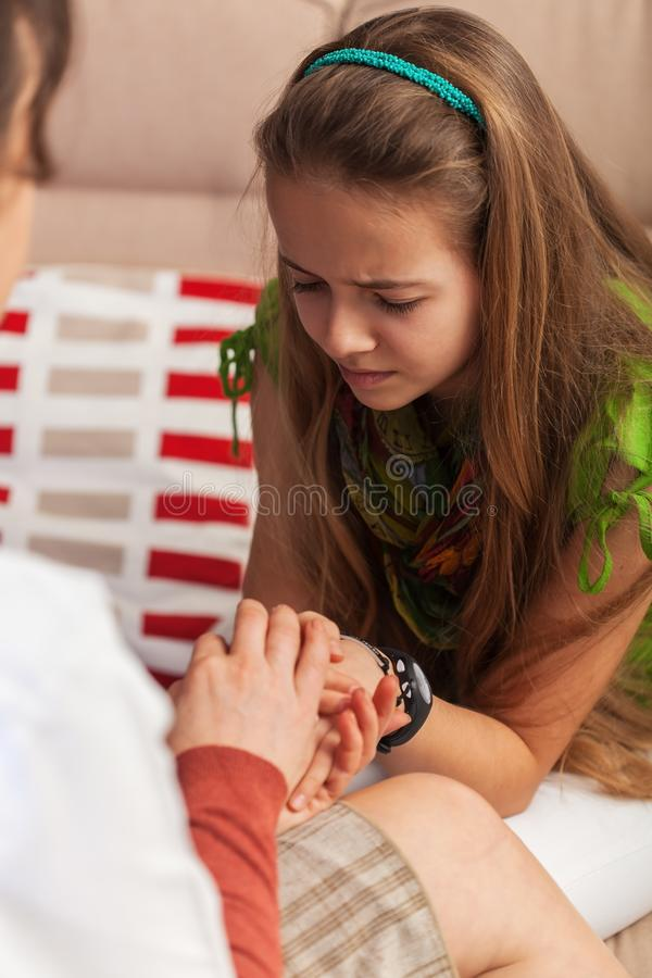Counseling professional woman trying to provide comfort to sad teenager girl - close up royalty free stock photography