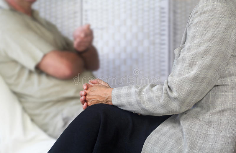Counseling session. Counseling therapist listening to patient sat on couch royalty free stock photography