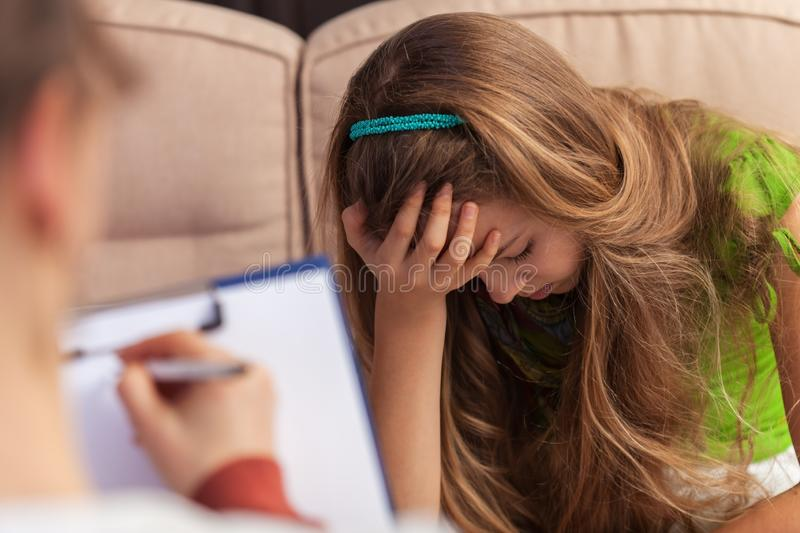 Counseling and support professional taking notes about a sad teenager girl - close up stock image