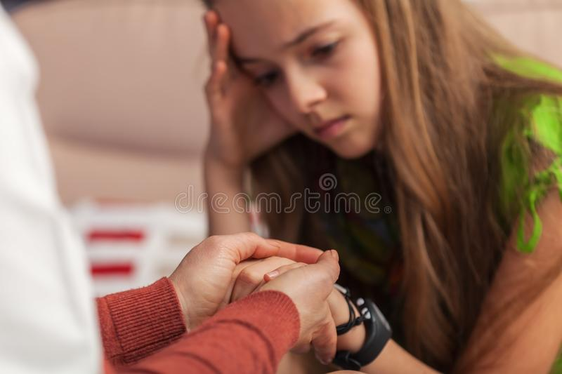 Counseling professional trying to provide comfort to sad teenager girl holding her hands - close up. Counseling and support professional trying to provide stock images