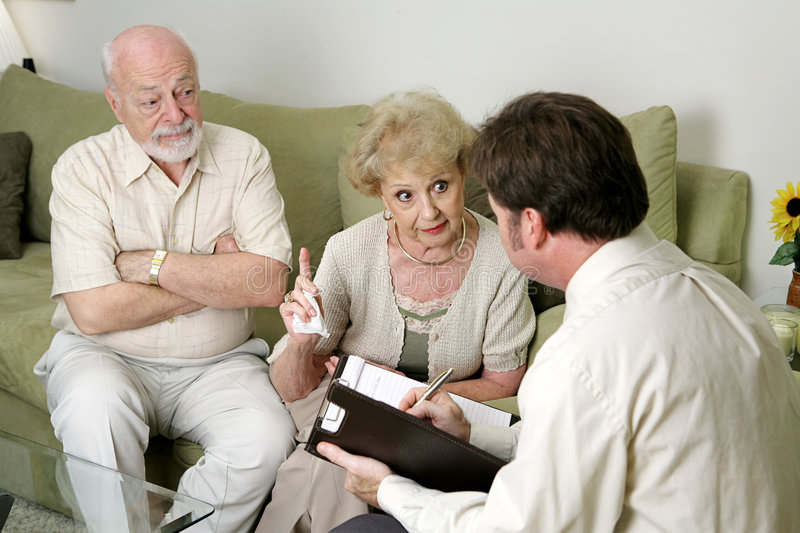 Counseling - You Won't Believe What He Does!. A senior couple in marriage counseling. She's complaining to the therapist about her husband while he looks on in stock images
