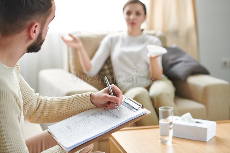 Counselor with document. Professional counselor making notes in document while listening to story of patient in front of him stock images