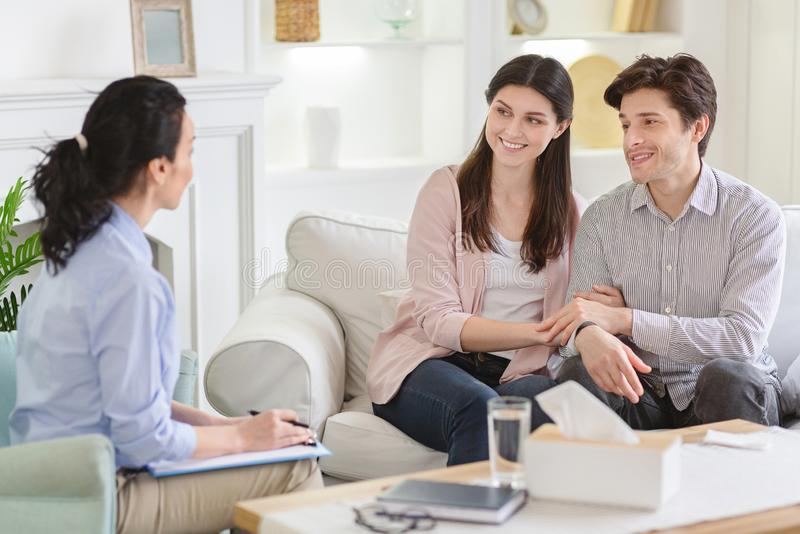 Counselor and happy couple after effective marital therapy. Men and women smiling to psychotherapist in office, empty space royalty free stock image