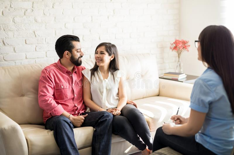 Reconciled couple after effective marital therapy. Counselor and happy young hispanic couple after effective marital therapy stock photos