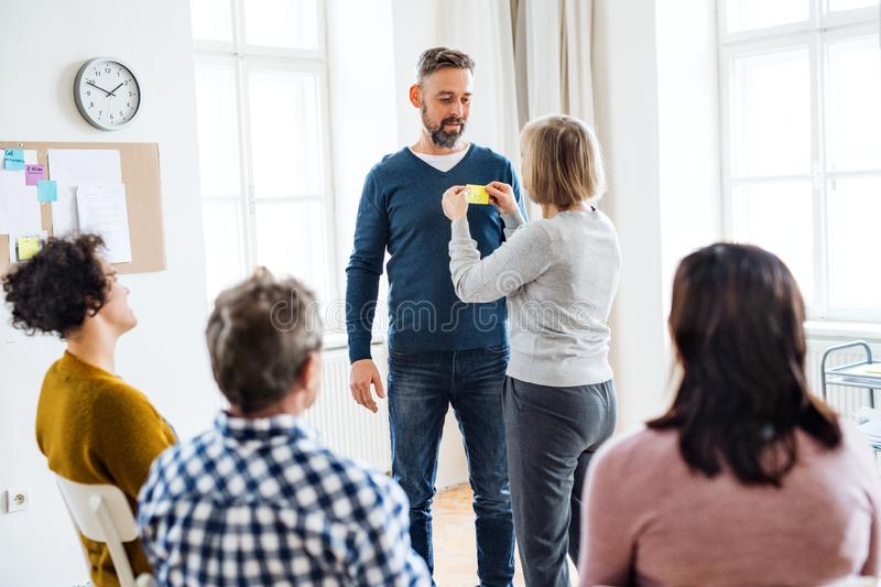 Counselor putting an adhesive note with the word sad on client during group therapy. royalty free stock images