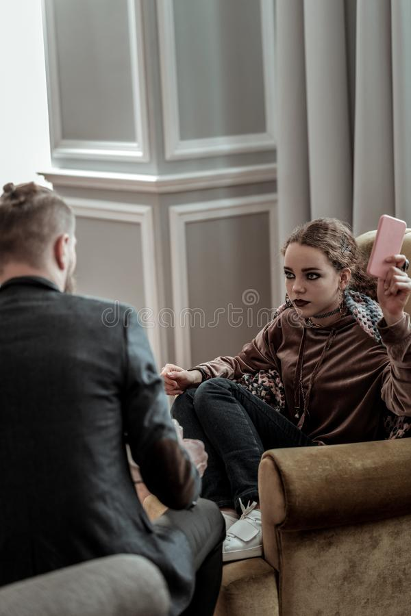 Counselor wearing dark jacket listening to depressed teenager. Depressed teenager. Professional counselor wearing dark jacket listening to depressed teenager stock photo