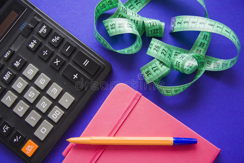 Count calories. With calculator and measuring tape stock photo