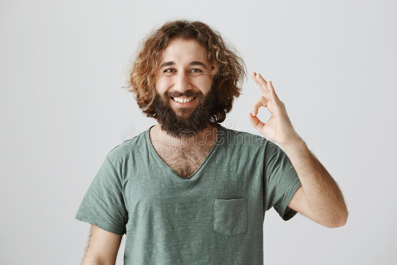 Count on me, deal is ours. Portrait of confident friendly easter male with beard and curly hair showing okay or great royalty free stock photos