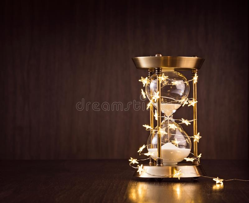 Countdown to Christmas or New Years. Christmas or new years countdown. Rustic Hourglass wrapped in lights with sand trickling through on a wooden background stock photo
