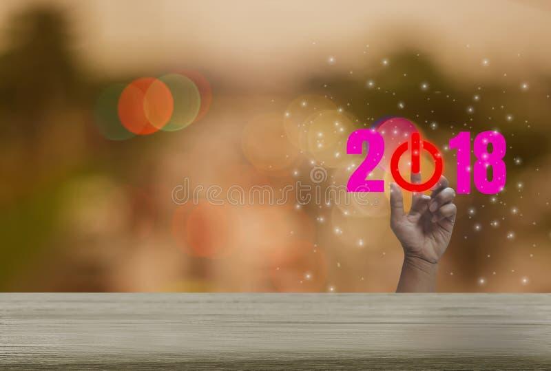 Countdownholztisch 2018 mit buntem bokeh Hintergrund Funkeln und festlicher Ferienzeit, Handpressen des abstrakten Begriffs stockfoto