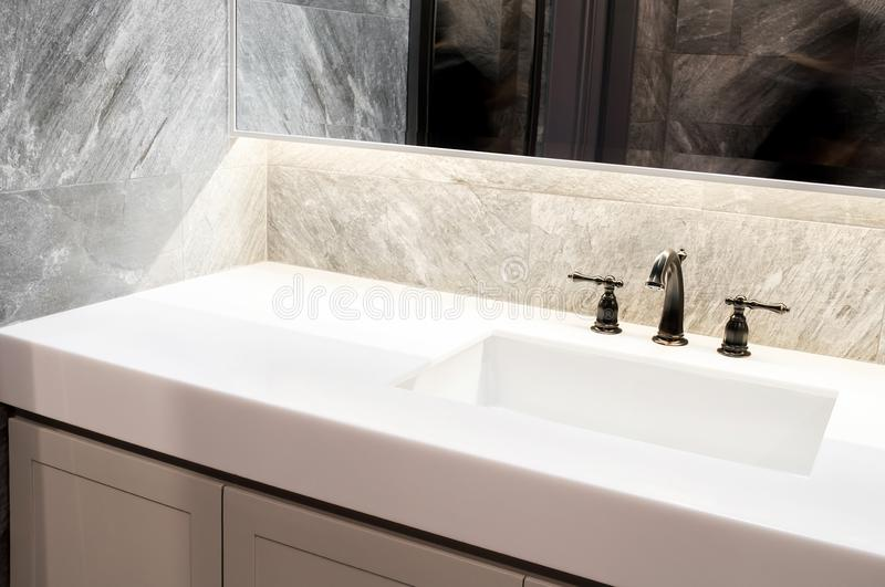 Counter top white marble,quartz with washbasin.Wall and floor beige,grey marble stone tile interior design of restroom or toilet b royalty free stock photo