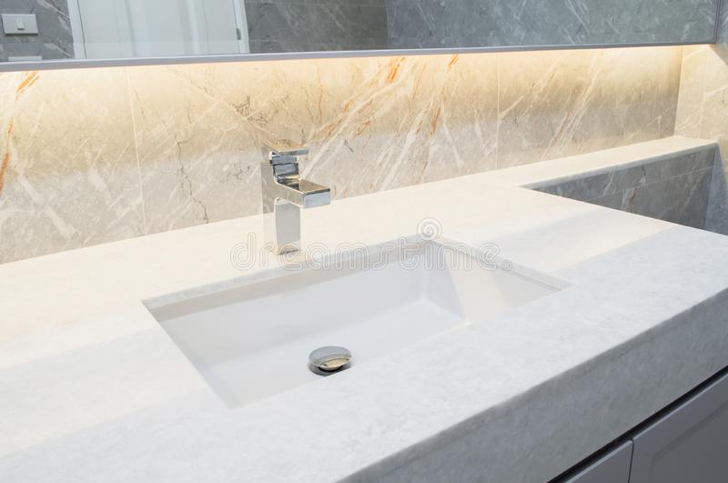 Counter top white marble with washbasin.Wall and floor beige,grey marble stone interior design of restroom or toilet background.Re stock photo