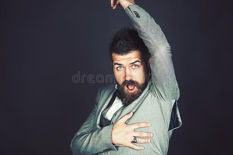 Counterfeit and fake clothing. Bad quality concept. Hipster with beard with ripped hole on seam. Bearded man look at. Torn coat with surprise. Fashion model stock images