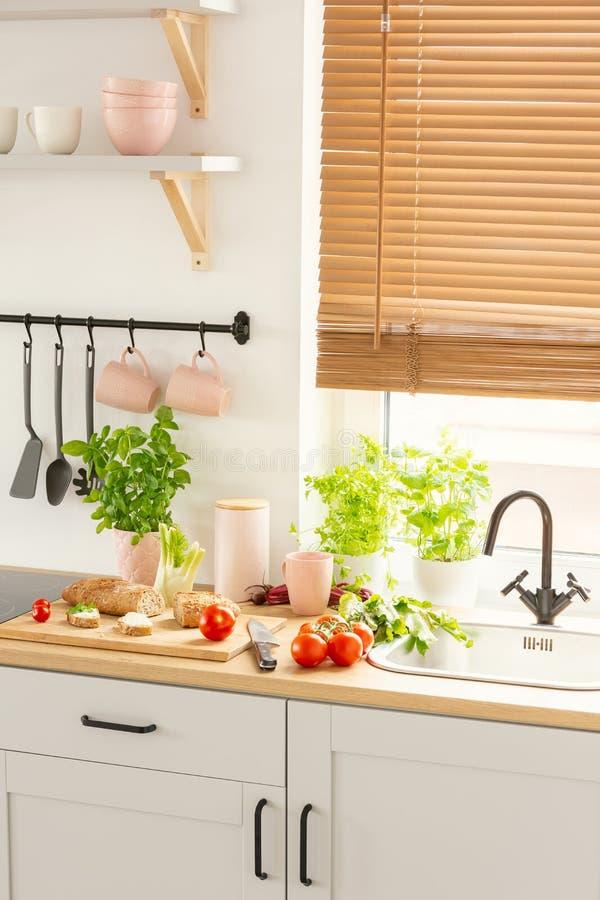 Countertop z chlebem na drewnianej desce, świeżych pomidorach i zielonych roślinach w jaskrawym kuchennym wnętrzu z okno z storam obrazy stock