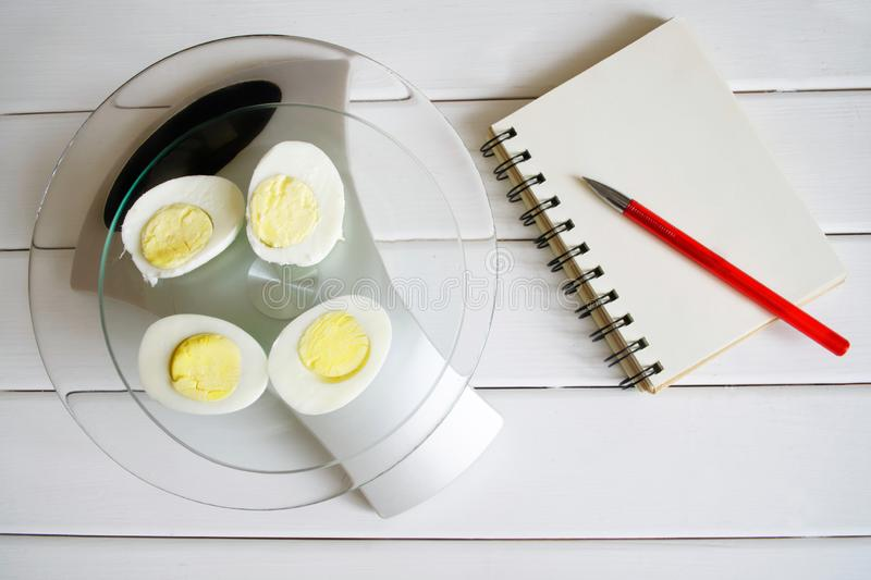 Counting the amount of protein, calories, carbohydrates and fats in food. Chicken egg on the kitchen scales. Slim figure, fitness, weight loss, diet and proper royalty free stock photos
