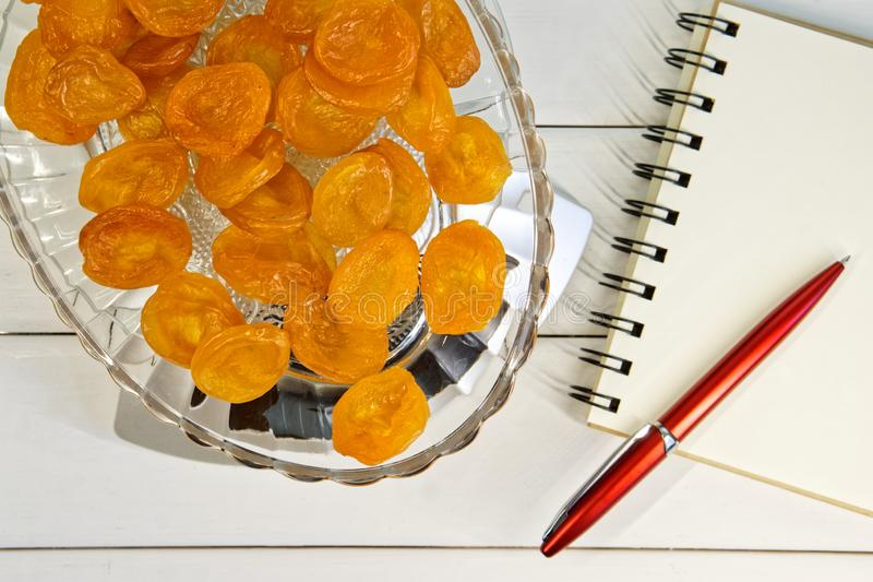 Counting calories, proteins, fats and carbohydrates in food. Dried fruits - apricots in a transparent plate on a kitchen scale. Slim figure, diet, weight loss stock photography