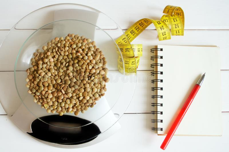 Counting calories, proteins, fats and carbohydrates in food. Lentil grains on table scales. Slim figure, diet, weight loss and proper nutrition royalty free stock photo