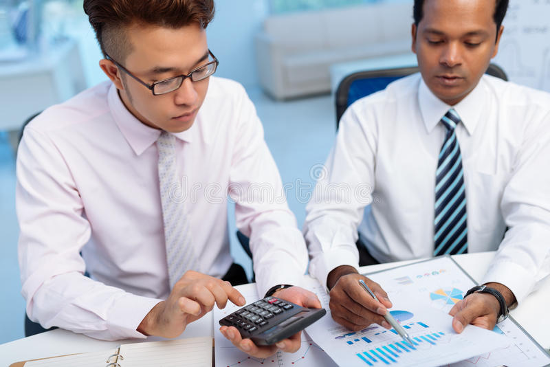 Counting expenses. Two serious Asian financial managers counting expenses royalty free stock photos