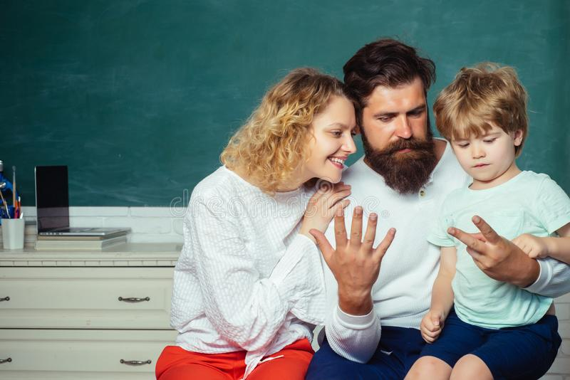 Counting on fingers. Happy young couple who are standing with their son at graduation. First time to school. First day. At school. Educational process royalty free stock images