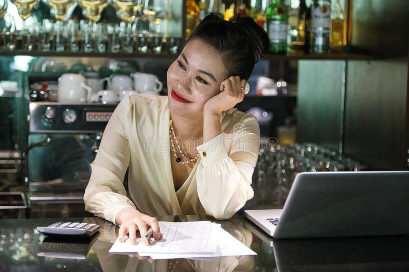 Counting income. Happy pretty restaurant owner smiling when counting income royalty free stock images