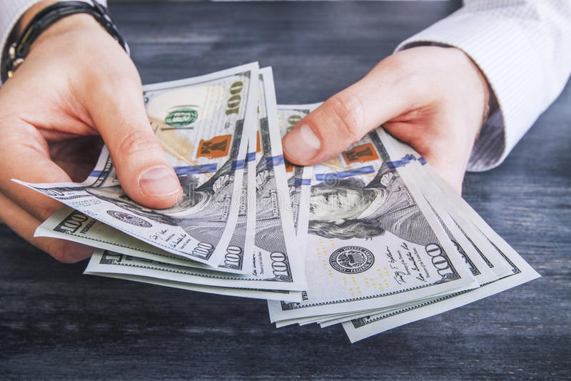 Counting money. Caucasian hands counting dollar banknotes on dark wooden surface stock photography