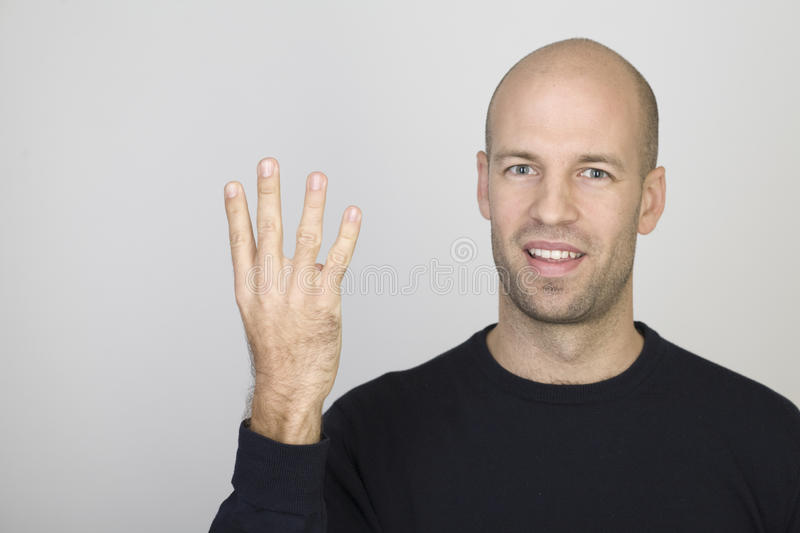 Counting number 4. Young man counting with his fingers the number four royalty free stock images