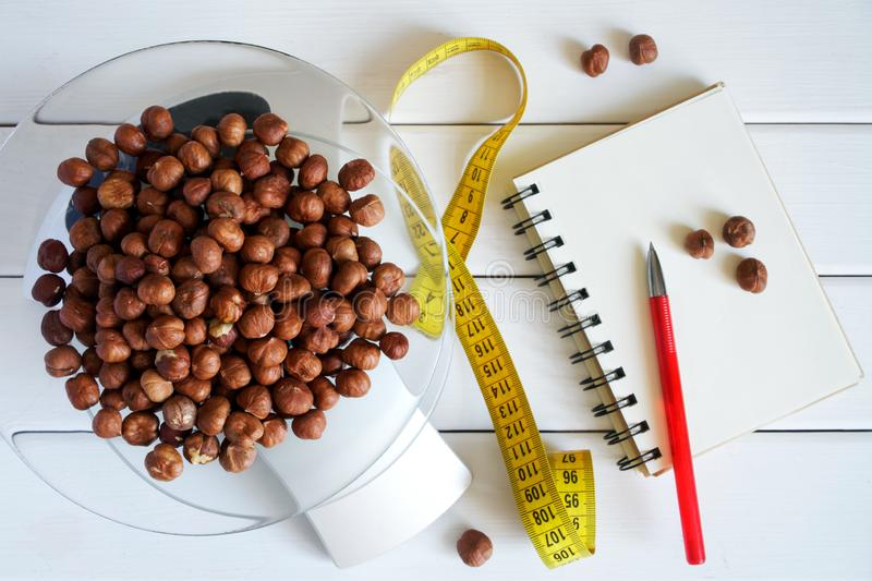 Counting and recording the amount of calories, proteins, carbohydrates and fats in food. Hazelnut on kitchen scales. Slim figure, fitness, weight loss, diet royalty free stock images