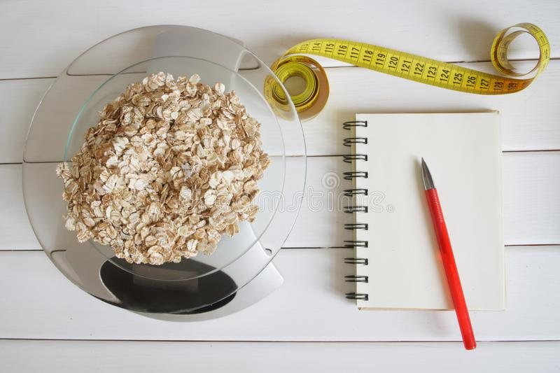 Counting and recording the amount of carbohydrates, calories, proteins and fats in food. Flakes from four cereals on kitchen. Scales. Oatmeal, wheat, barley and stock photo
