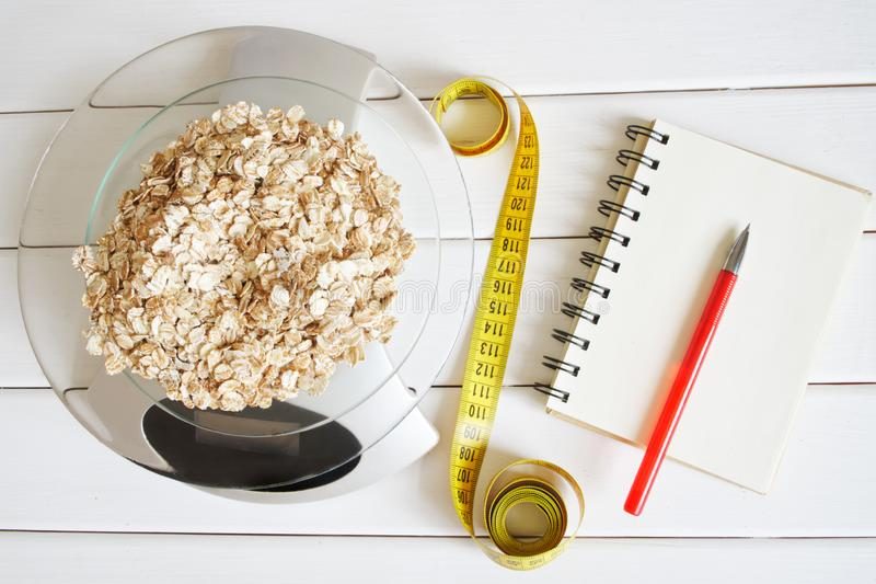 Counting and recording the amount of carbohydrates, proteins, calories and fats in food. Flakes from four cereals on kitchen. Scales. Oatmeal, wheat, barley and royalty free stock photos