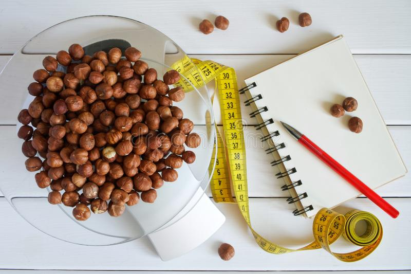 Counting and recording the amount of protein, calories, carbohydrates and fats in food. Hazelnut on kitchen scales. Slim figure, fitness, weight loss, diet and stock images