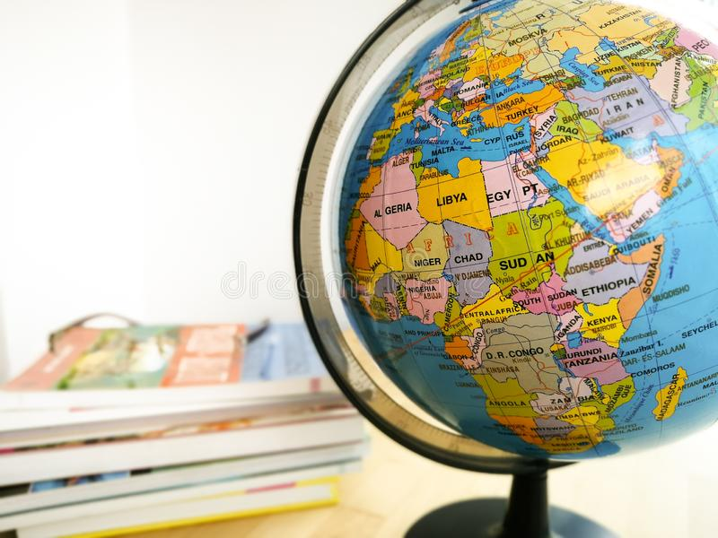 Countries and continents close up with the color map on a globe with books in the background. royalty free stock photography