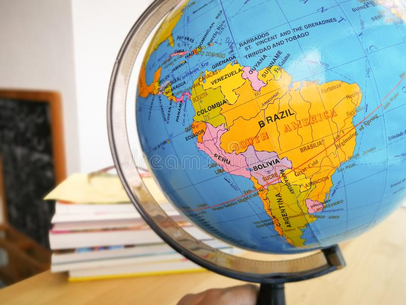 Countries and continents close up with the color map on a globe with books in the background. stock images