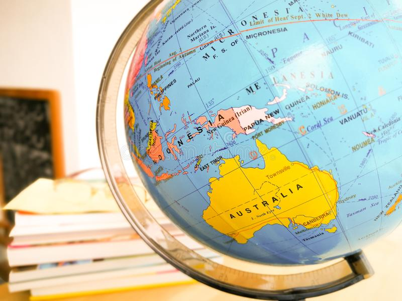 Countries and continents close up with the color map on a globe with books in the background. royalty free stock photos