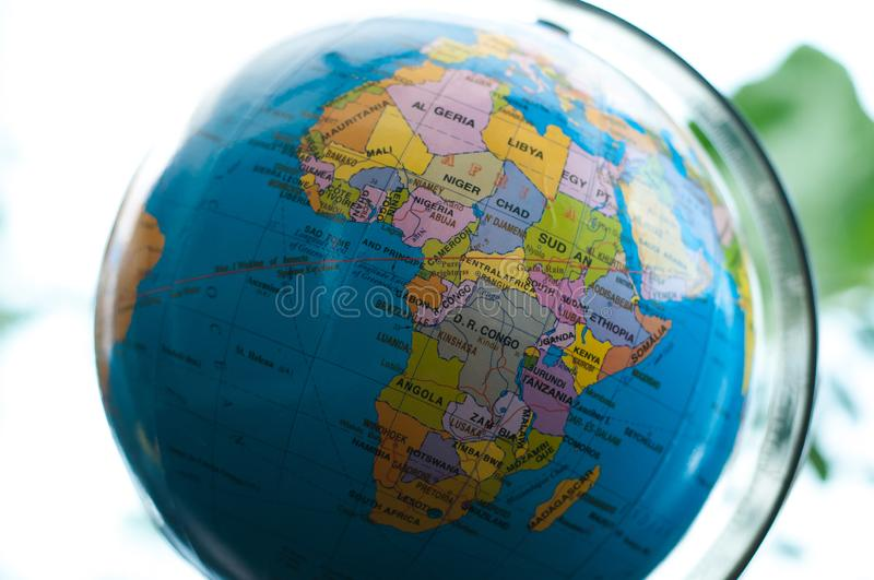 Countries and continents close up with the color map on a globe with books in the background. stock photos