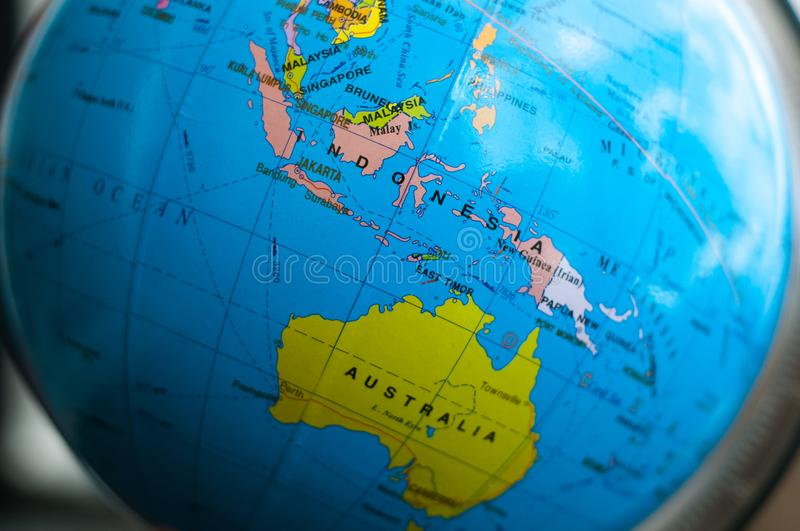 Countries and continents close up with the color map on a globe with books in the background. royalty free stock image