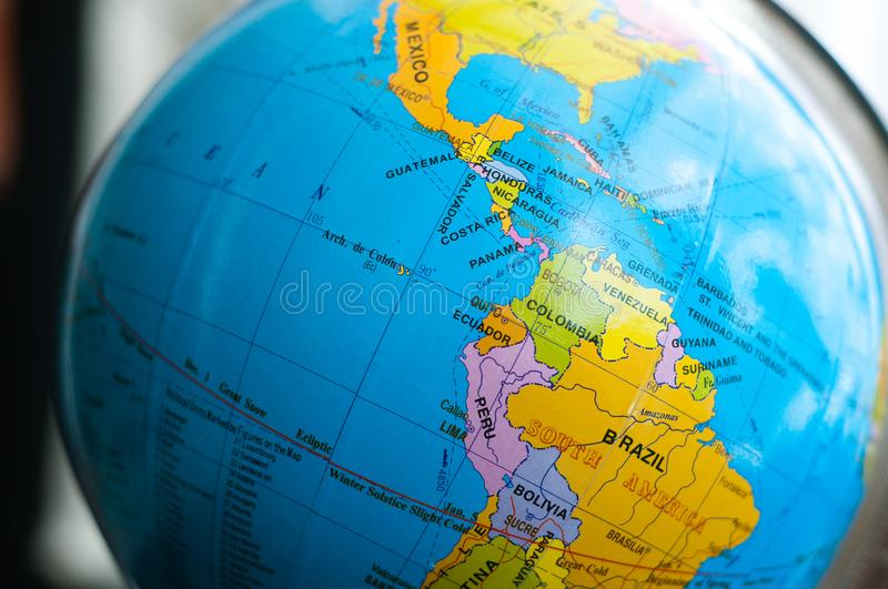 Countries and continents close up with the color map on a globe with books in the background. stock photo