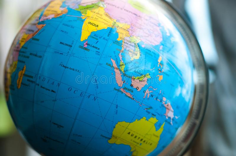 Countries and continents close up with the color map on a globe with books in the background. stock image