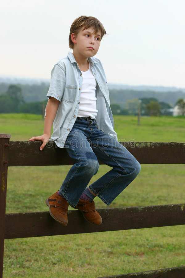 Country boy sitting on a fence royalty free stock image